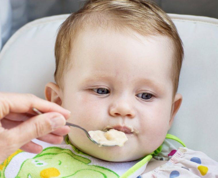 bebe aburrido alimentado con cuchara