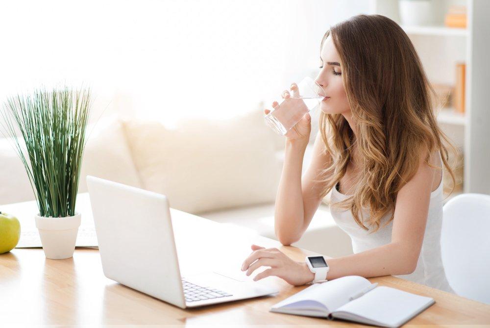 mujer tomando agua para un colon saludable