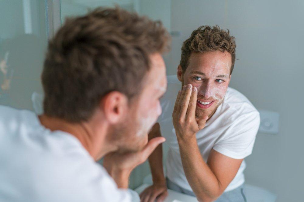 Hombre lavándose la cara acné