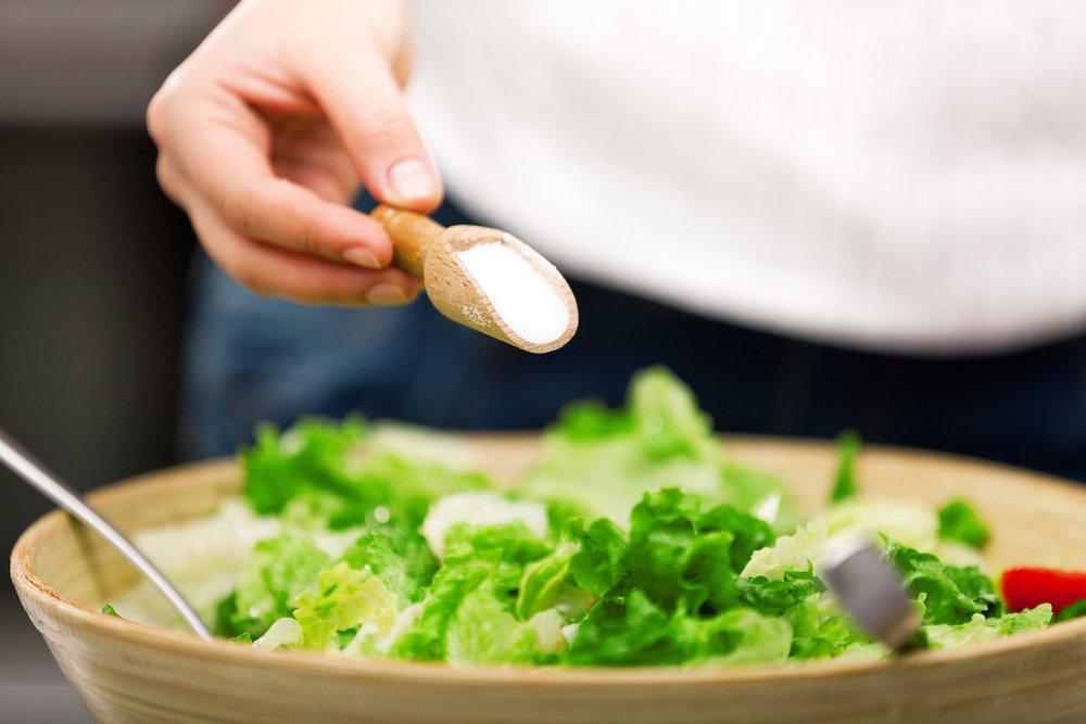 persona poniendo sal en una ensalada