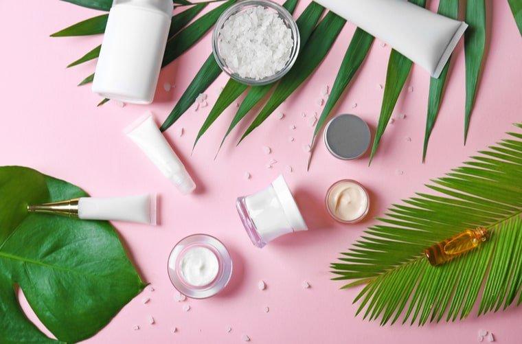 Productos de belleza en fondo rosado
