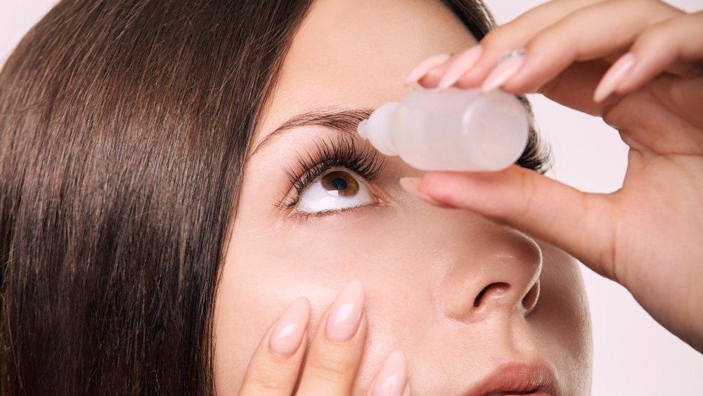 Mujer poniendo gotas en sus ojos