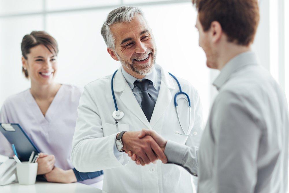 Médico estrechando la mano con un paciente