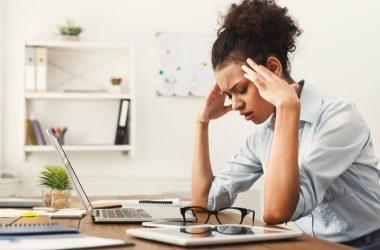 Mujer-sentada-en-su-escritorio-con-migraña