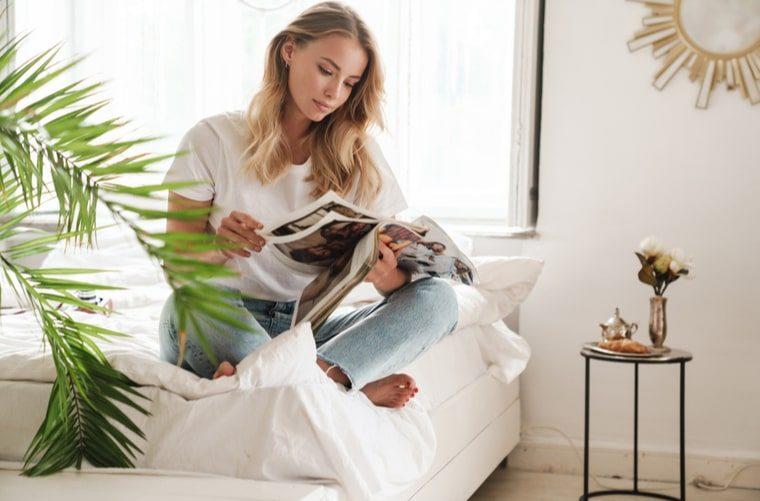 Mujer en casa leyendo revista