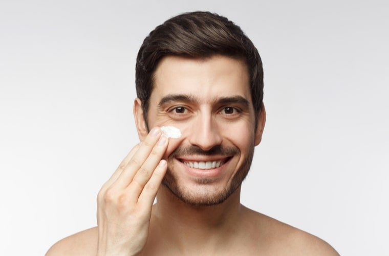 Hombre aplicándose crema en la cara