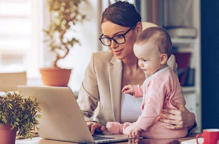 Mujer en el pc con bebé en brazos