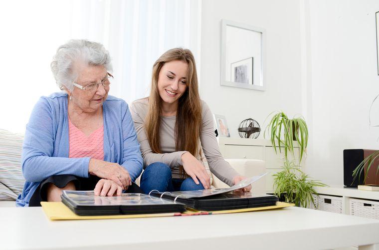 Mujer ve fotos con abuela con Alzheimer